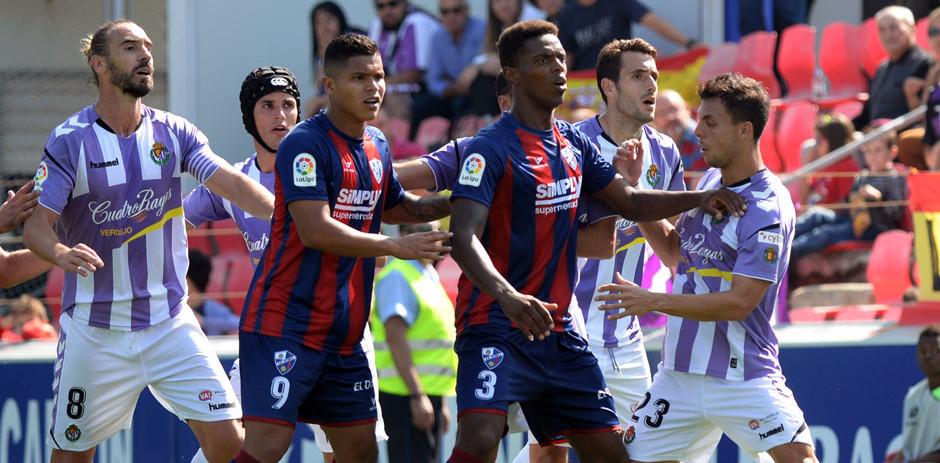 Jugadores del Real Valladolid y oscenses, en una acción de estrategia del duelo liguero en Huesca <em><strong>(RealValladolid.es)</strong></em>