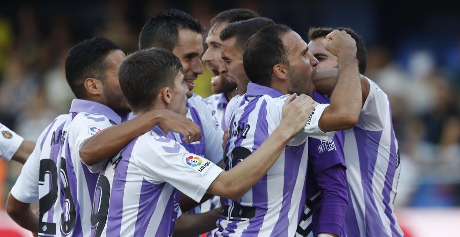 Los jugadores del Real Valladolid se abrazan a Jordi Masip tras repeler el penalti de Gerard Moreno | <em><strong>Foto: LaLiga</strong></em>